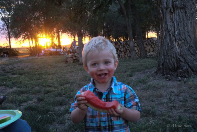A little dirt and watermelon juice make for a happy boy.